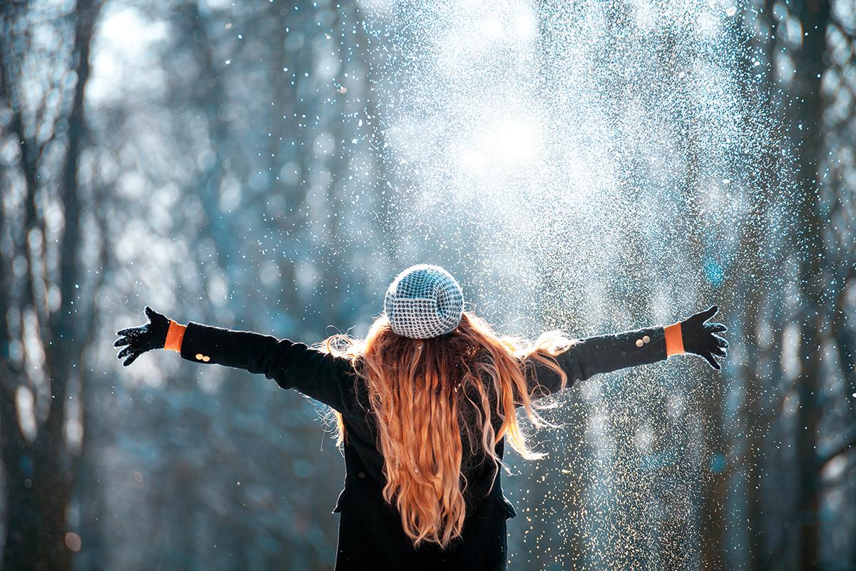 Femme de dos avec un bonnet ouvre grand les bras, neige qui tombe