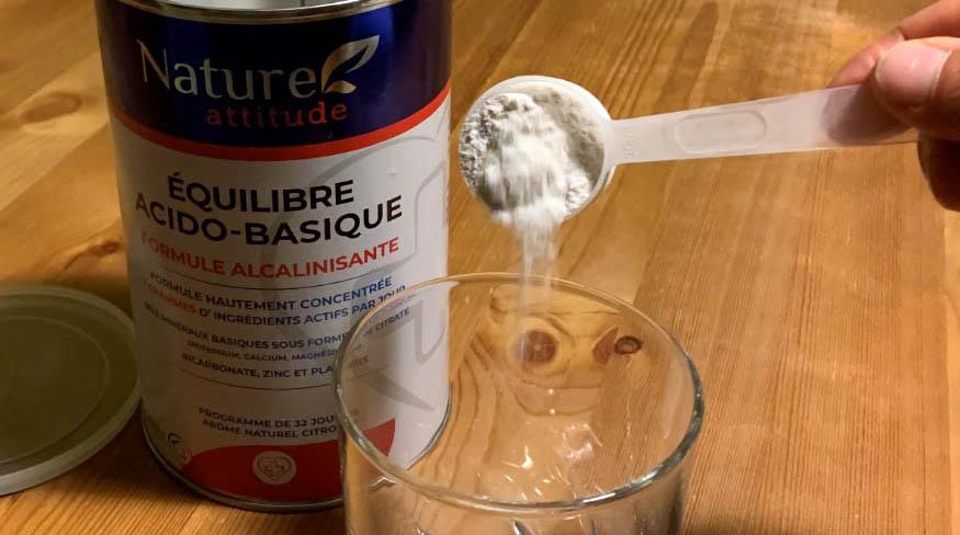 récipient en verre rempli d'un smoothie à la myrtille avec des myrtilles tout autour.